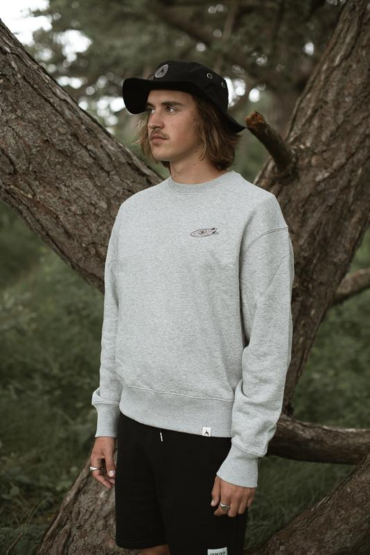 Young Man Looking Up In The Sky Standing In The Woods Near A Tree Wearing A Black Surfer Bucket Hat And Grey Crewneck