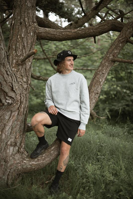 Young Man Sitting On A Tree Branch Wearing Collab Of Hands For Feet And Inmind Clothing Grey Crewneck