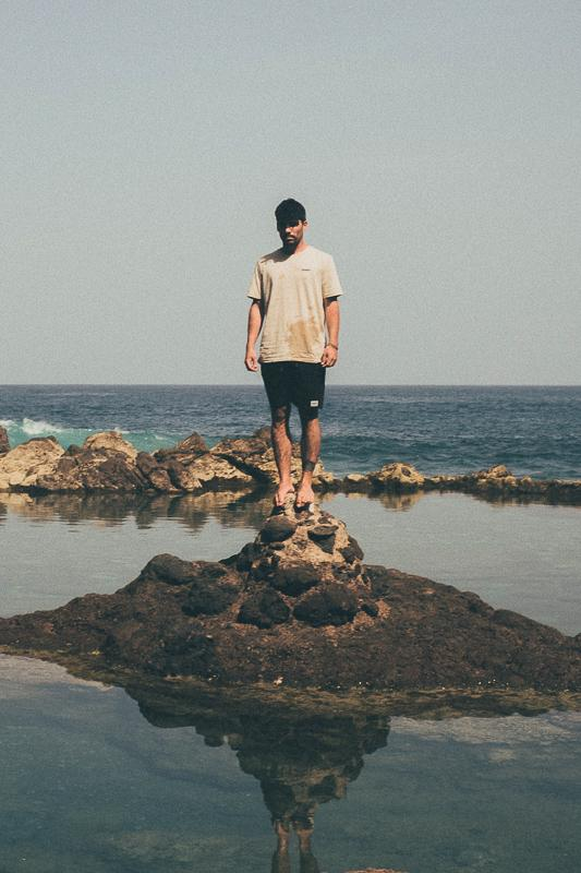 Man Standing On Rocks On Island, Inmind X Hands For Feet