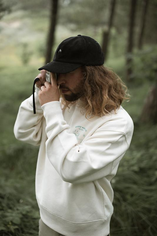 Man Taking Picture With Analog Vintage Camera In The Woods Wearing Organic Cotton Crewneck And Black Corduroy Cap