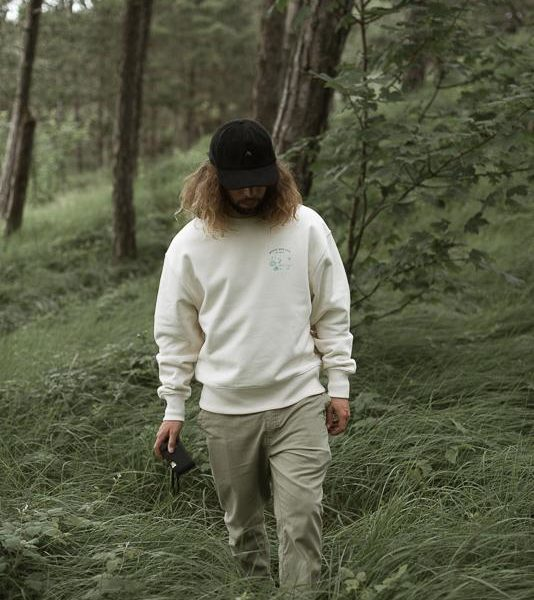 Worry Way Less Crewneck man standing in the green woods with trees and grass on the background wearing a crewneck of organic cotton with small screenprinted design chest front
